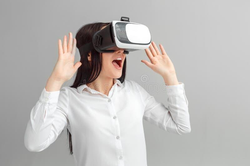 фристайл Женщина в положении шлемофона виртуальной реальности изолированная на сером наблюдая возбужденном видео стоковые изображения