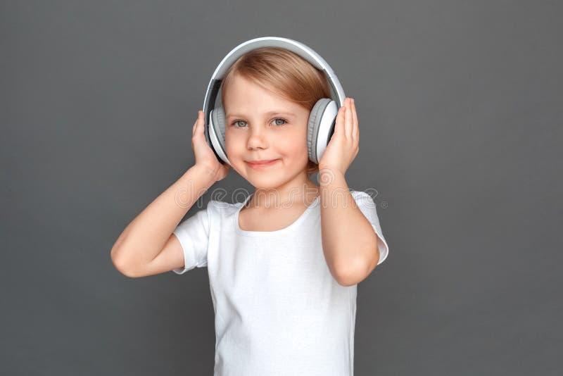 фристайл Маленькая девочка в наушниках изолированных на серый слушая усмехаться музыки радостный стоковые изображения