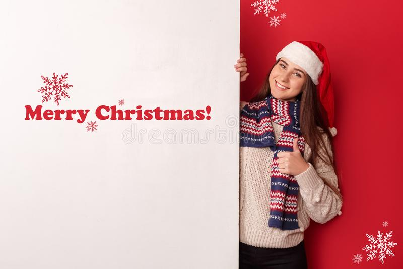 фристайл Положение шарфа молодой женщины нося и шляпы santa изолированное на красном цвете с большим пальцем руки белой доски вве стоковое изображение rf
