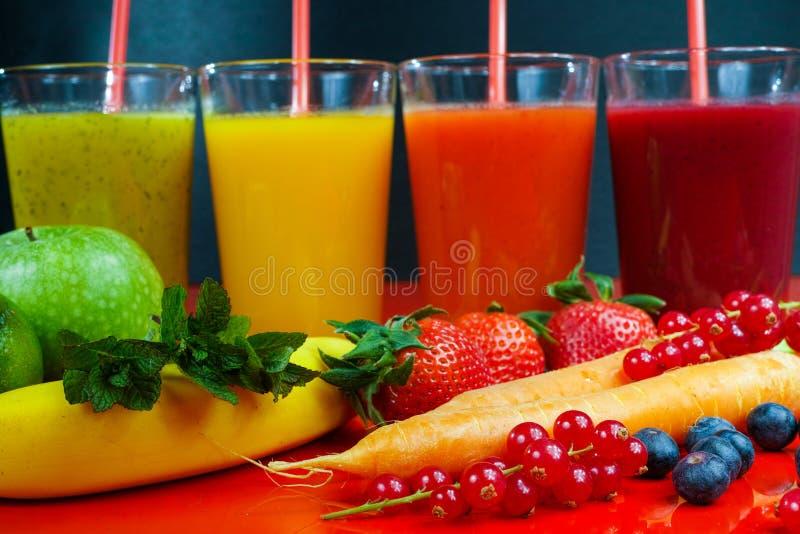 Фруктовые соки Colofrul свежие отжатые в высокорослых стеклах с плодоовощами стоковая фотография rf