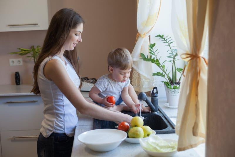 Фрукты и овощи мытья сына мамы кухни стоковые фото