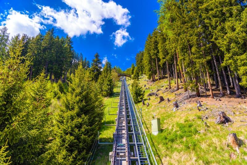 Фуникулярная дорога в лесе горных вершин, Давос, Graubuenden, Швейцарии стоковые изображения rf