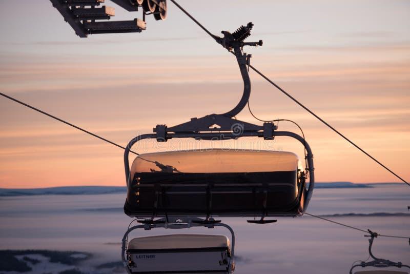 Фуникулярные подъемы/железная дорога кабеля поднимаются в Альпы Волшебный туман вокруг Изумительный заход солнца, идет снег совсе стоковое фото rf