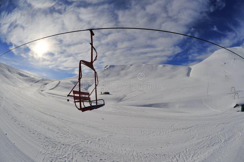 Фуникулер катания на лыжах над снежными наклонами в горы стоковая фотография