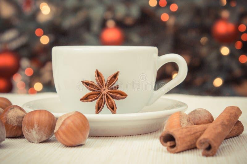 Фундуки, специи, чашка кофе или чай и рождественская елка с светами в предпосылке стоковое изображение rf