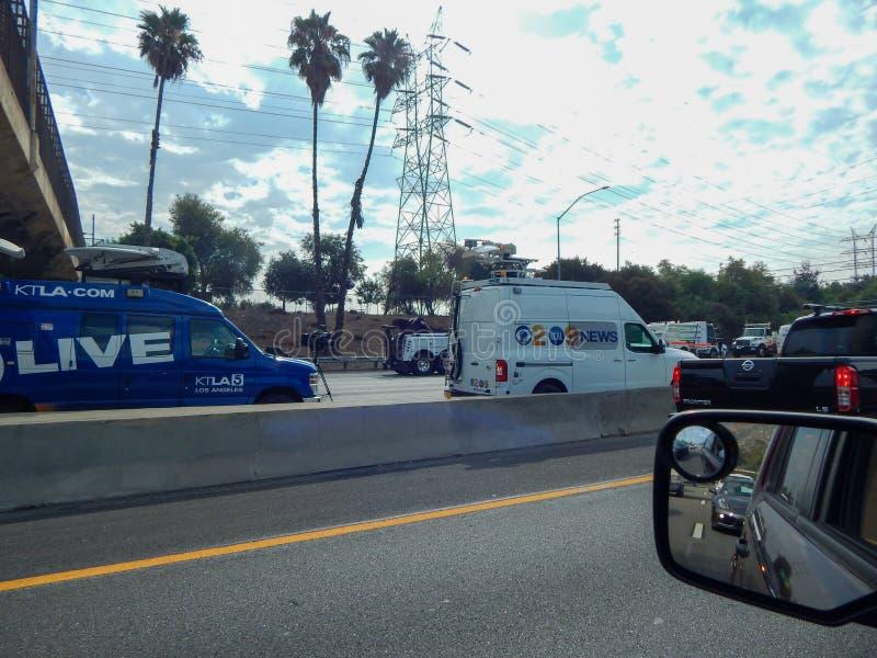 Фургоны новостей выравнивают скоростное шоссе во время аварии переворачиванной тележки на скоростном шоссе 5 в Лос-Анджелесе стоковые изображения