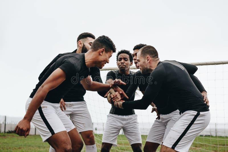 Футболисты держа их руки стоя в груде и веселя вверх Футболисты стоя около стойки ворот в a стоковое изображение rf