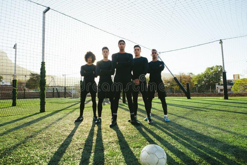 Футболисты стоя совместно на тангаже стоковые изображения