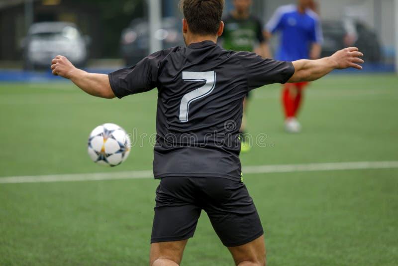 Футболист в футбольном поле гонит шарик в действии стоковые изображения rf