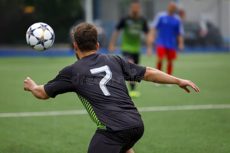 Футболист в футбольном поле гонит шарик в действии стоковое изображение
