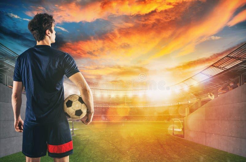 Футболист готовый для игры с шариком в его руках на выходе тоннеля раздевалки стоковое фото