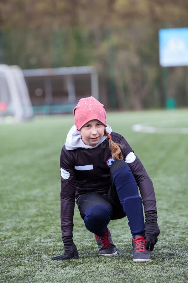 Футболист девушки выправляет гетры в ботинках футбола, сидя на зеленом поле стоковое изображение rf