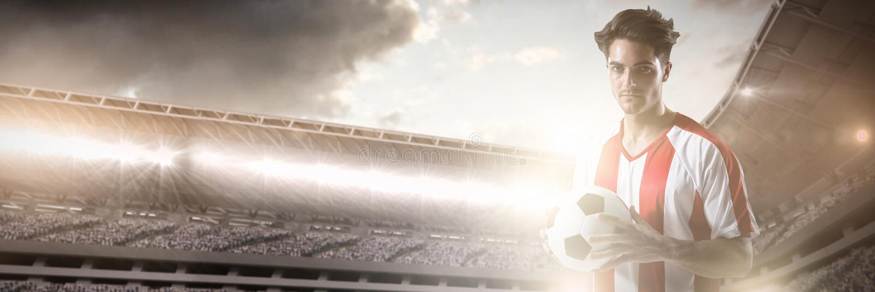 Футболист держа футбол с обеими руками против составного изображения Спорт-арены с поддержкой стоковое изображение rf