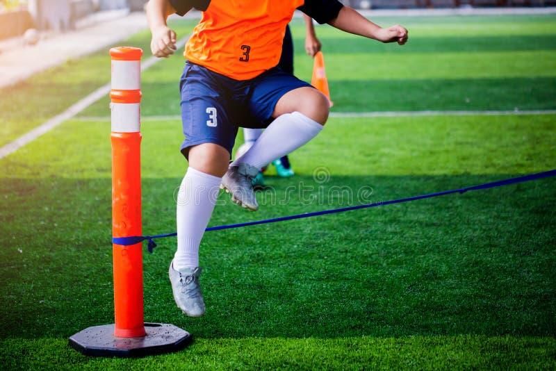 Футболист мальчика выполнить сверла координации и прочности путем скакать над веревочкой на на зеленой искусственной дерновине стоковые изображения