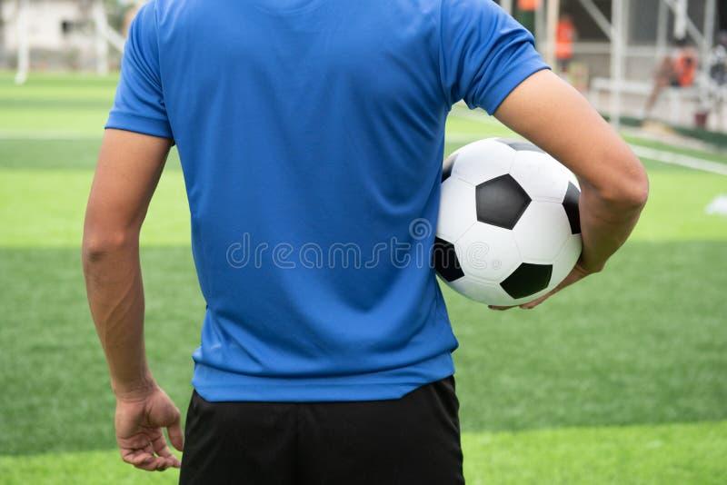 Футболист нося голубую рубашку, черные брюки раненые стоковое фото