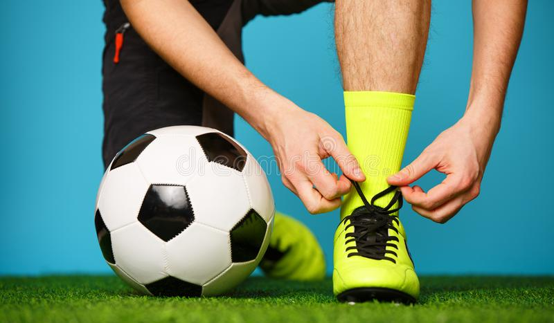 Футболист связывая его ботинки стоковая фотография rf
