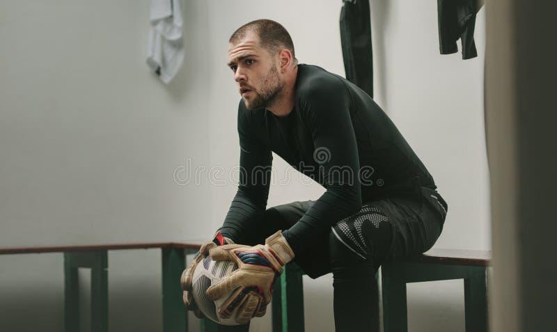 Футболист сидя в уборной держа футбол стоковое фото