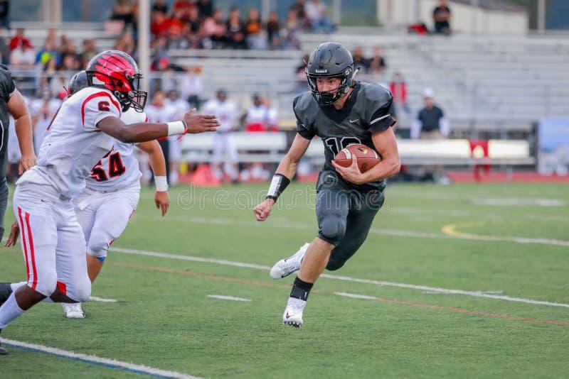Футболист средней школы бежать с шариком стоковое фото