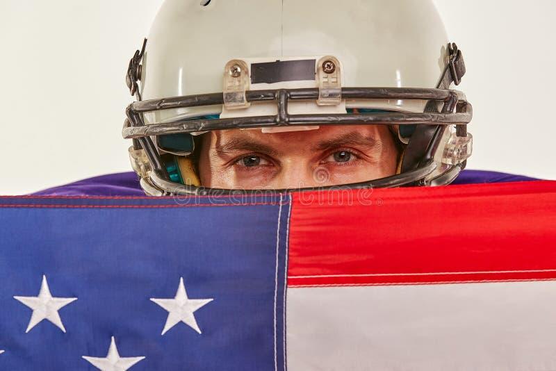 Футболист с формой и американский флаг гордый его страны, на белой предпосылке стоковые фото