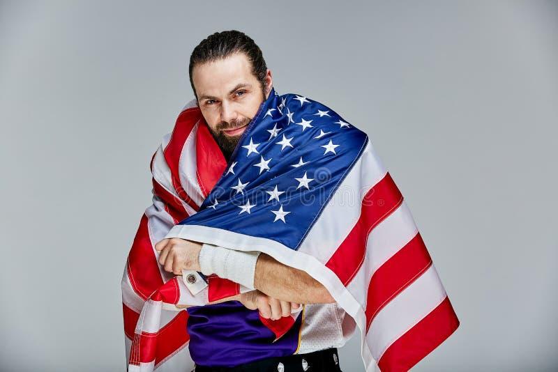 Футболист с формой и американский флаг на его плечах гордых его страны, на белой предпосылке стоковое фото