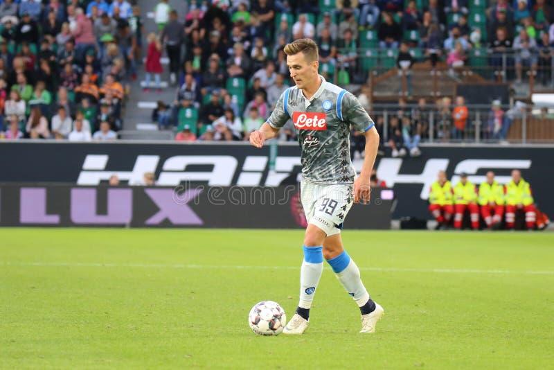 Футболист Arkadiusz Milik в действии во время футбольного матча стоковая фотография