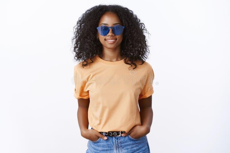 Футболка солнечных очков привлекательной крутой стильной Афро-американской девушки нося оранжевая держа карманы рук уверенный, ус стоковое изображение rf