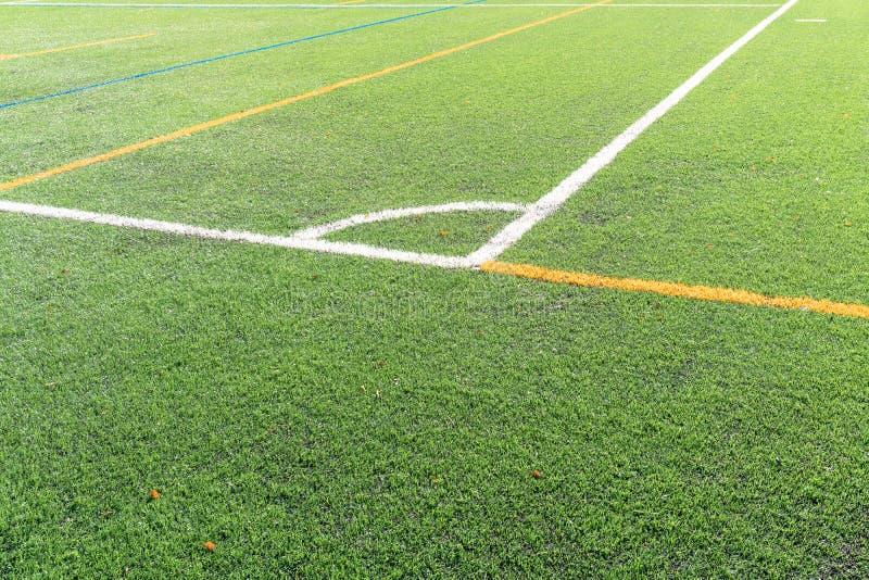 Футбольное поле с новым искусственным полем дерновины, белая угловая маркировка конец вверх Предпосылка футбола скопируйте космос стоковое изображение rf