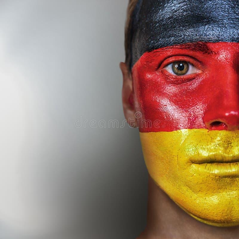 Футбольный болельщик при немецкий флаг покрашенный на его стороне стоковые фото