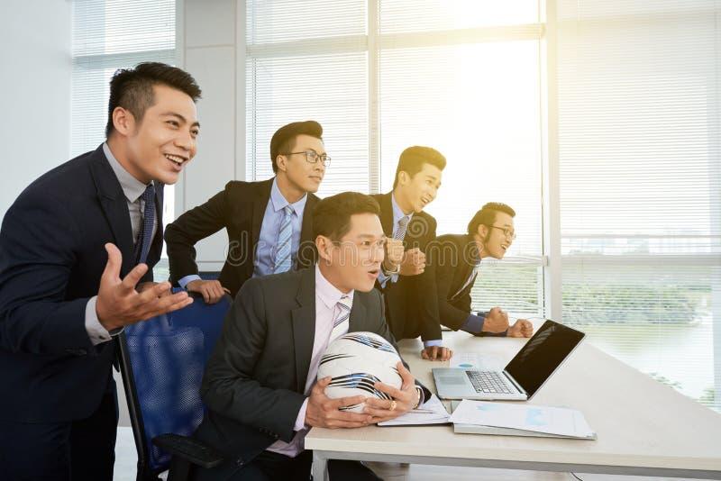Футбольный матч азиатского бизнесмена наблюдая стоковые изображения rf