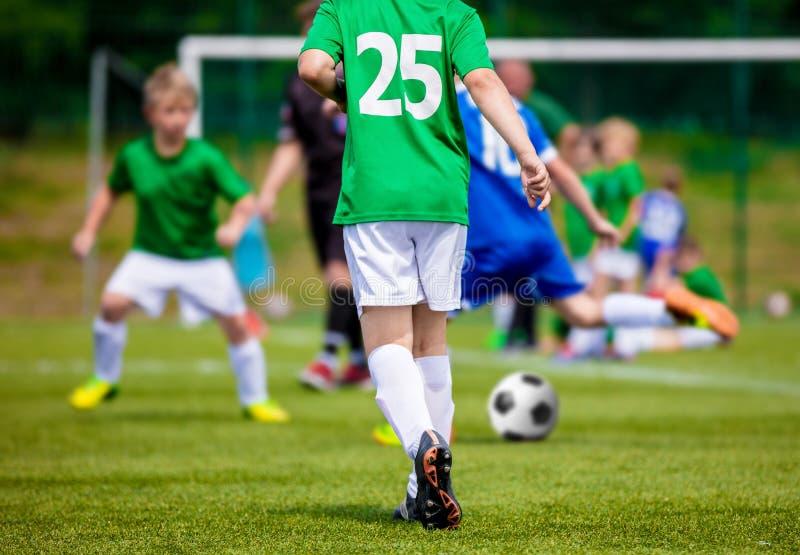 Футбольный матч футбола молодости Мальчики пиная футбольный мяч стоковые фото