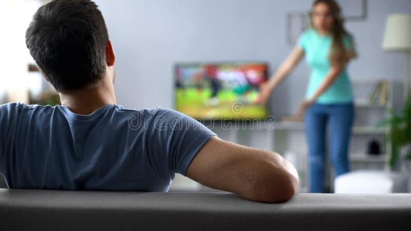 Футбольный матч человека наблюдая игнорируя конфликт с женщиной, кризис в отношениях стоковая фотография