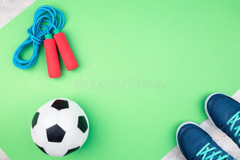 Футбольный мяч и скача веревочка на зеленой циновке стоковые изображения rf