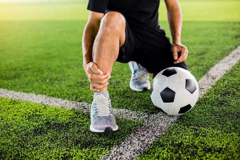 Футбольный мяч на зеленой искусственной дерновине с футболистом сидит и улавливает лодыжка стоковое изображение
