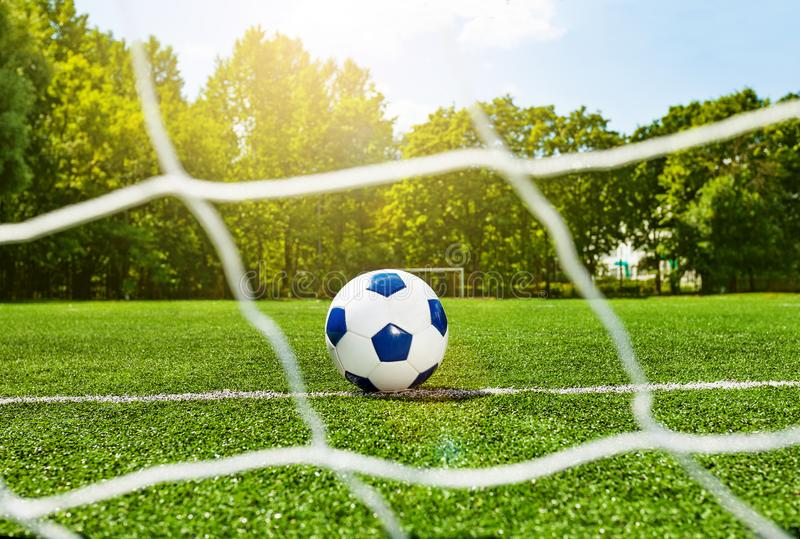 Футбольный мяч футбола за сетью строба на поле стоковое изображение rf