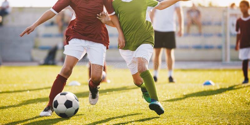 Футбол игры мальчиков Идущие футболисты футбола Дети на футбольном поле бежать с шариком стоковое изображение