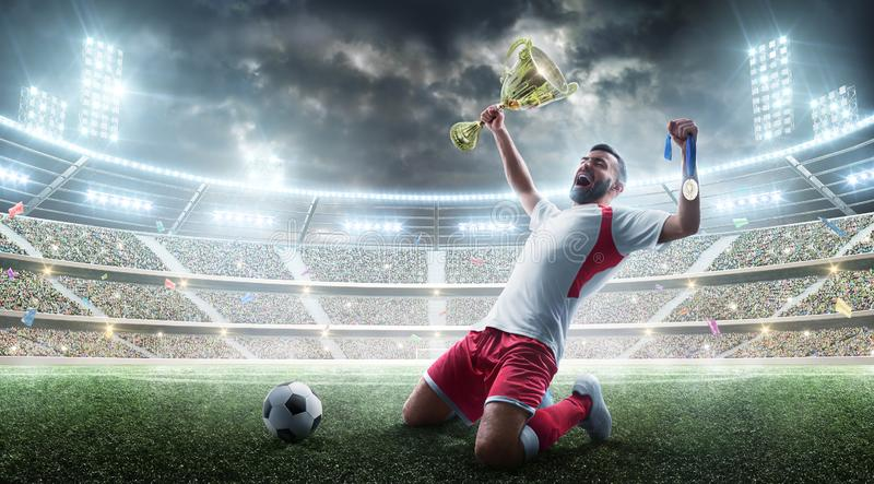 футбол Профессиональный футболист празднует выигрывать футбольного матча открытый стадион Футболист держит чашку и стоковая фотография rf