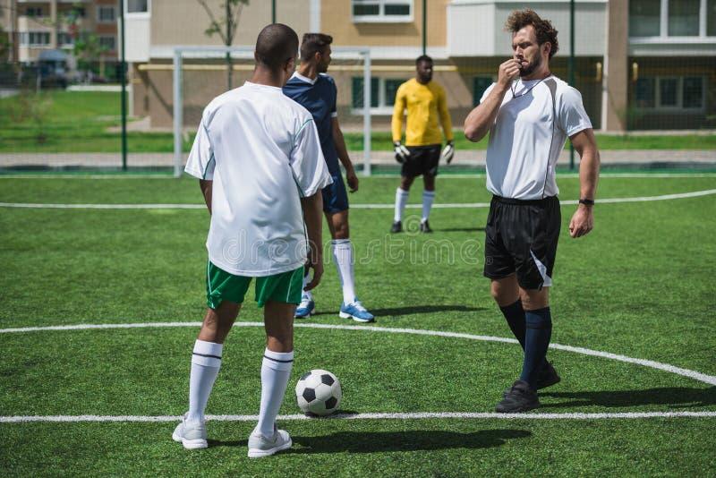 Футболисты во время футбольного матча на тангаже стоковые фото