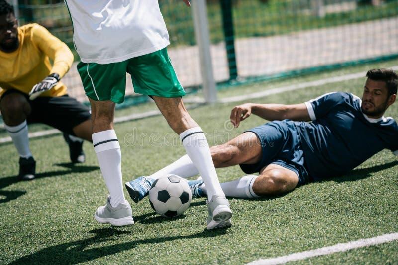 Футболисты играя футбол на тангаже совместно стоковая фотография rf