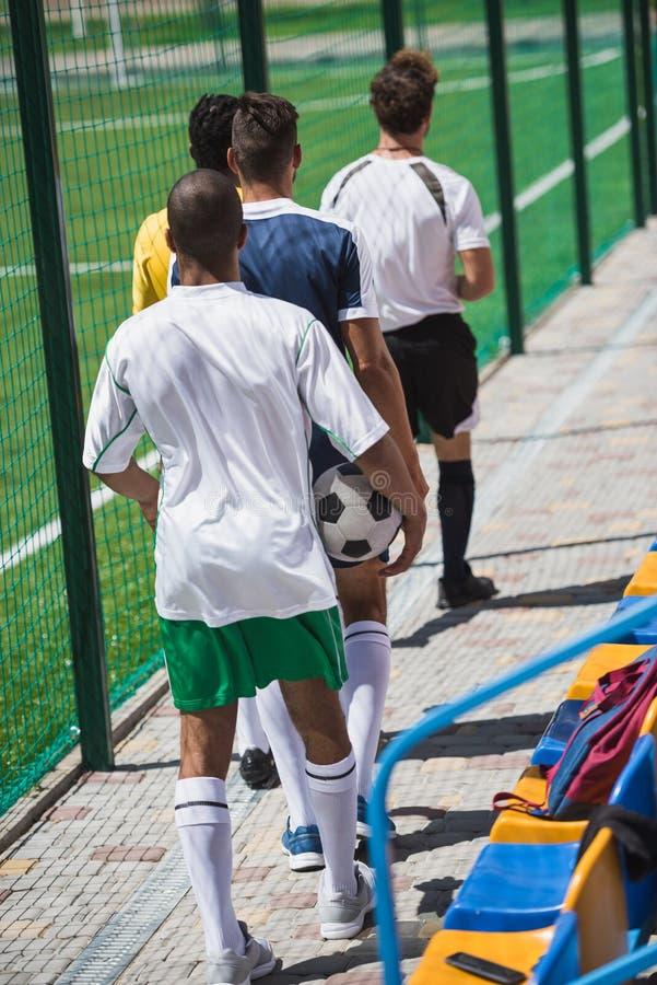 Футболисты и рефери идя на тангаж футбола стоковые изображения rf