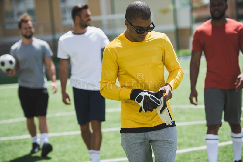 Футболисты идя на тангаж перед футбольным матчем стоковое фото rf
