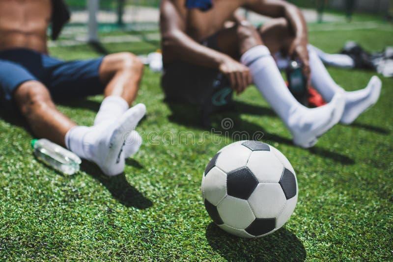 Футболисты отдыхая на футбольном поле с футбольным мячом стоковое фото