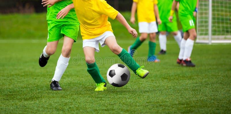 Футболист бежать с шариком на тангаже Молодые футболисты стоковые фотографии rf