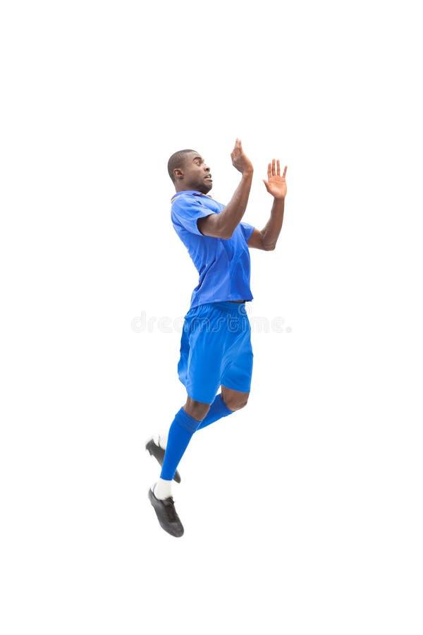Футболист в голубой скакать стоковая фотография