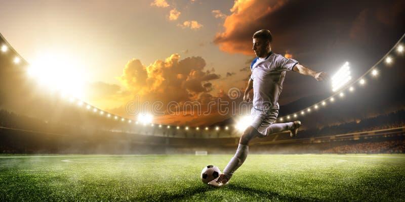 Футболист в действии на предпосылке панорамы стадиона захода солнца стоковые фотографии rf