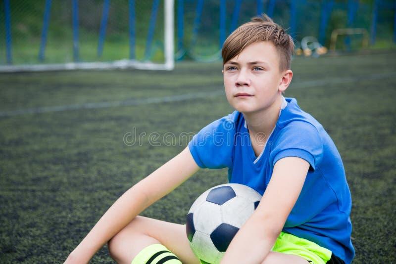 Футболист мальчика сидя на поле стоковая фотография