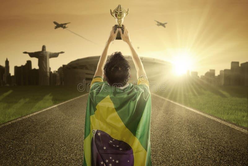 Футболист поднимая трофей на дороге стоковое изображение rf