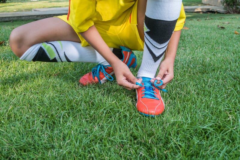 Футболист получая готовый для игры связывая его ботинки стоковое фото rf