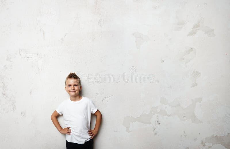 Футболка молодого мальчика нося белая и усмехаться на стоковые фото