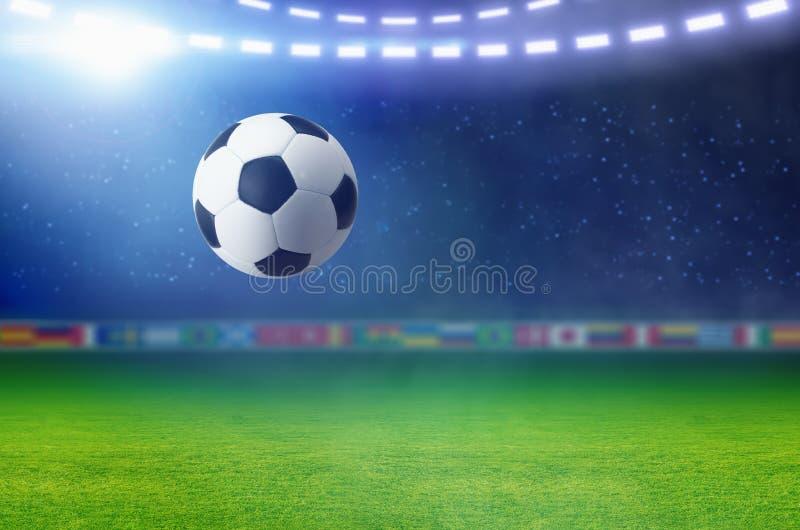 Футбольный мяч, яркая фара освещает зеленое футбольное поле стоковые фотографии rf