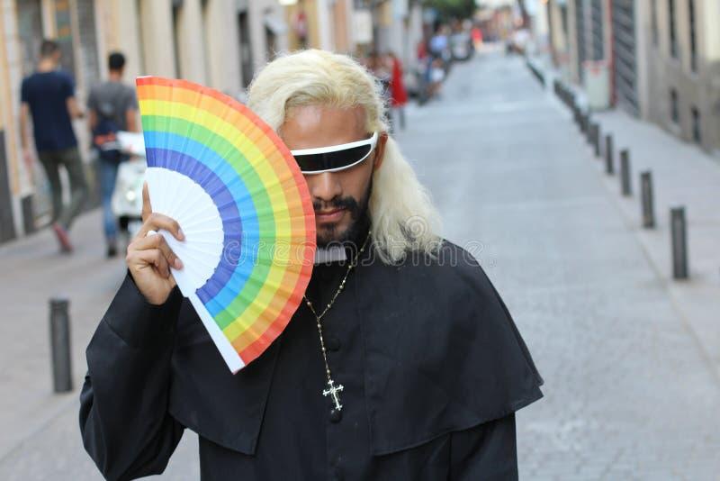 Футуристический смотря священник держа вентилятор радуги стоковая фотография rf